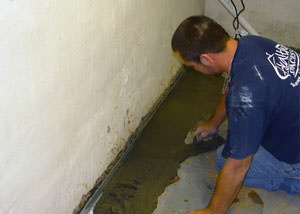 Restoring a concrete slab floor with fresh concrete after jackhammering it and installing a drain system in Ponoka.